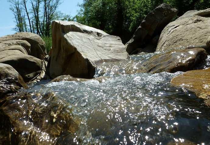 струя воды подмывает камень